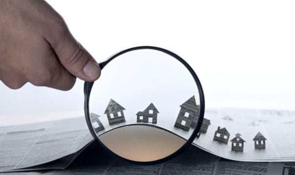 Hand holds the magnifying glass looking at paper houses.