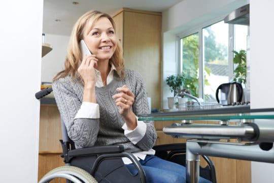 Woman in a wheelchair calling to ask about disability forgiveness for credit card debt