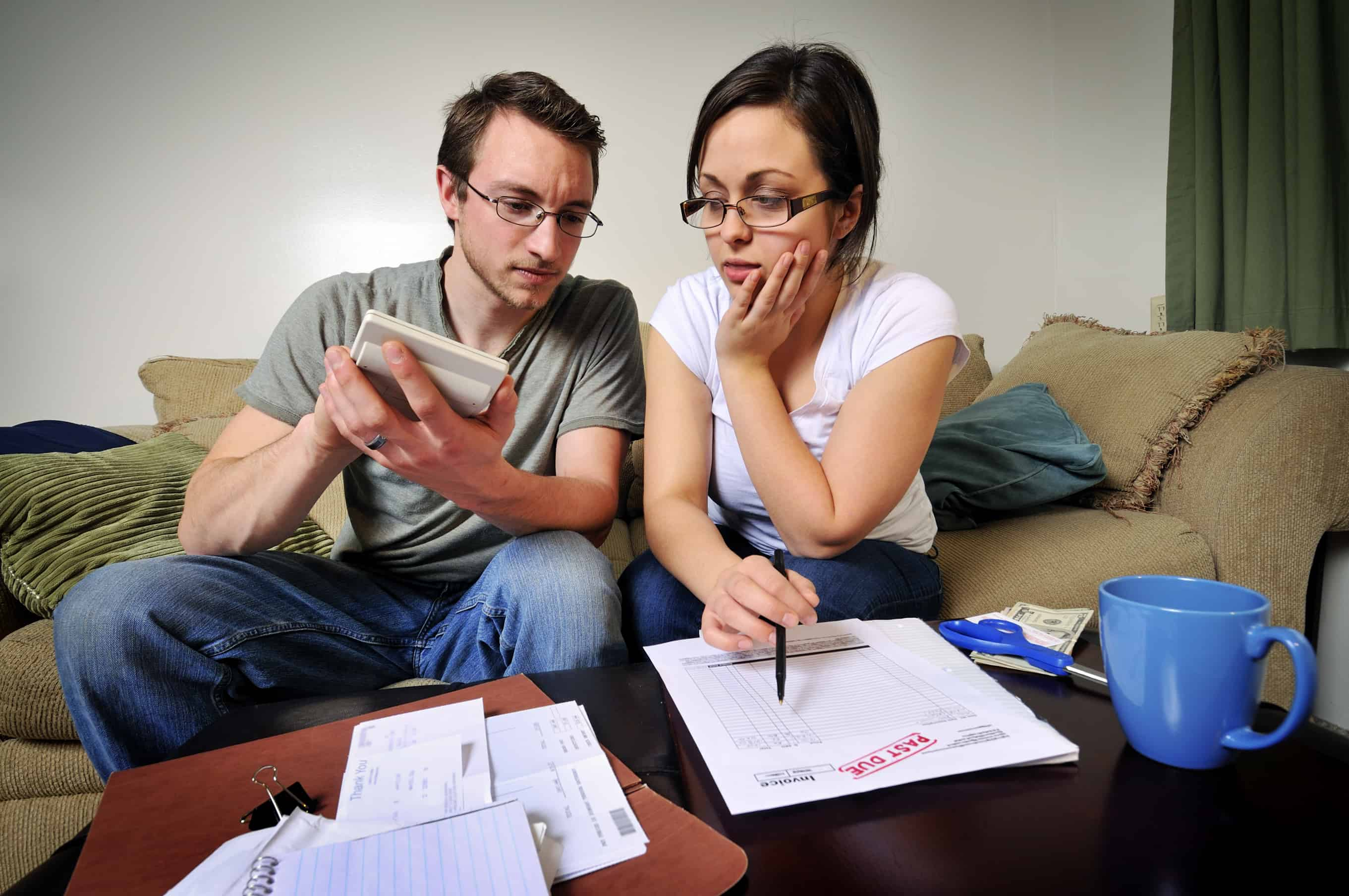 Young couple sitting on couch reviewing over due credit card statements.