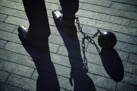 Working man in a suit is chained to his job