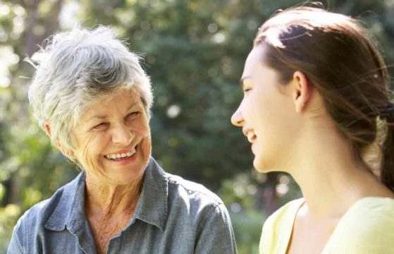 Grandmother talking with teenage granddaughter on bench