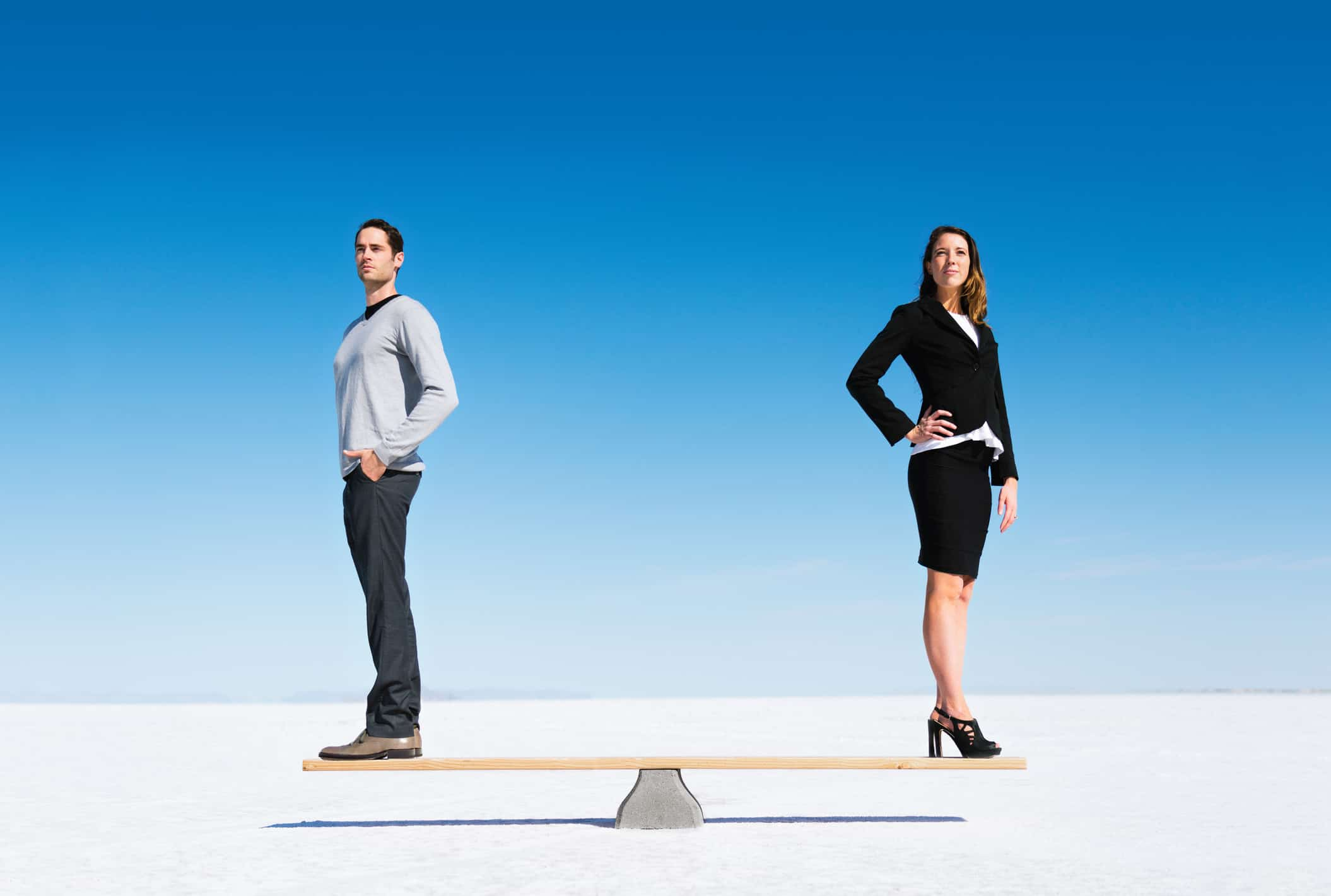 Businesswoman and businessman balanced on Seesaw.