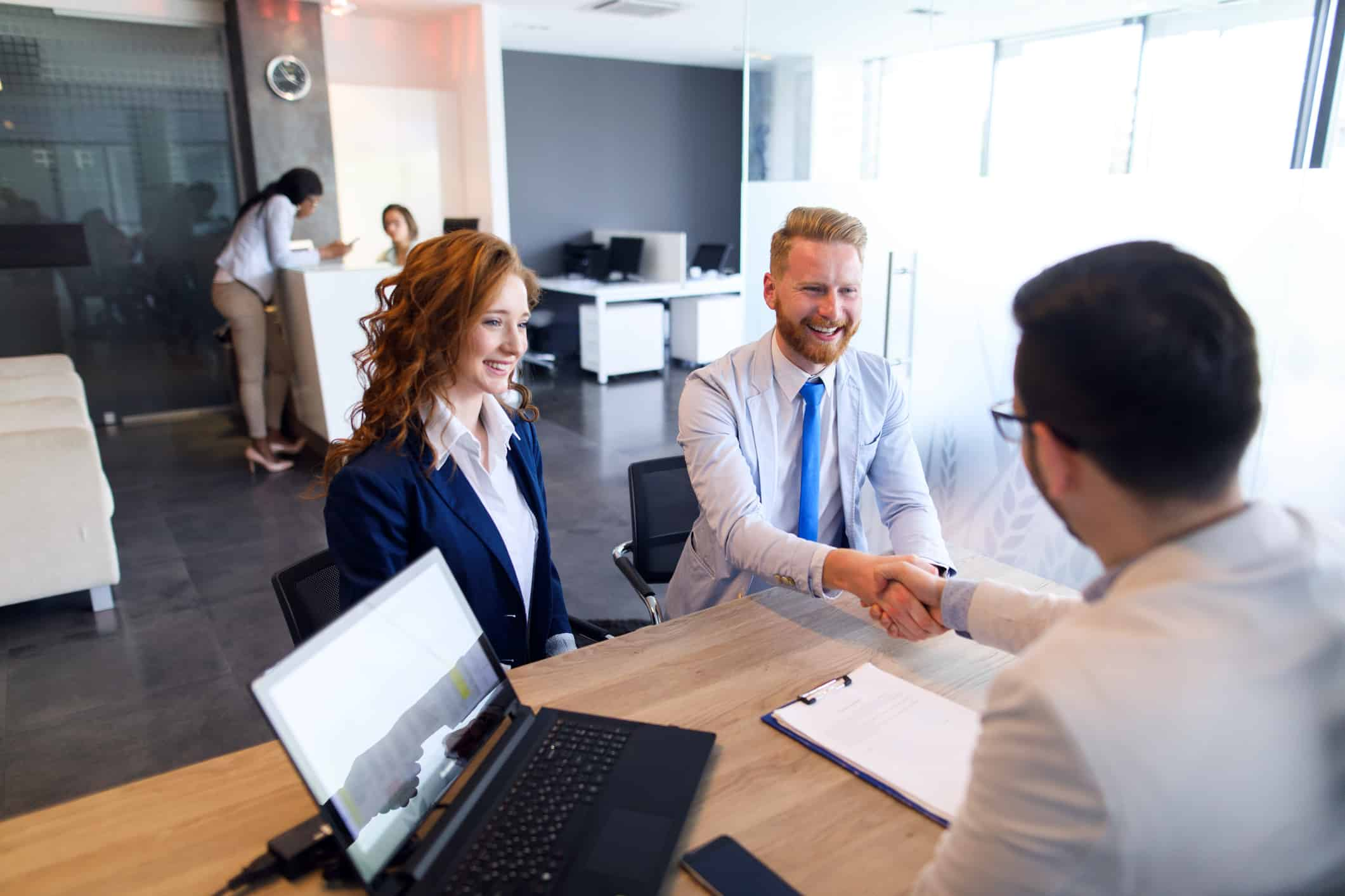 Young couple talk to loan officer.
