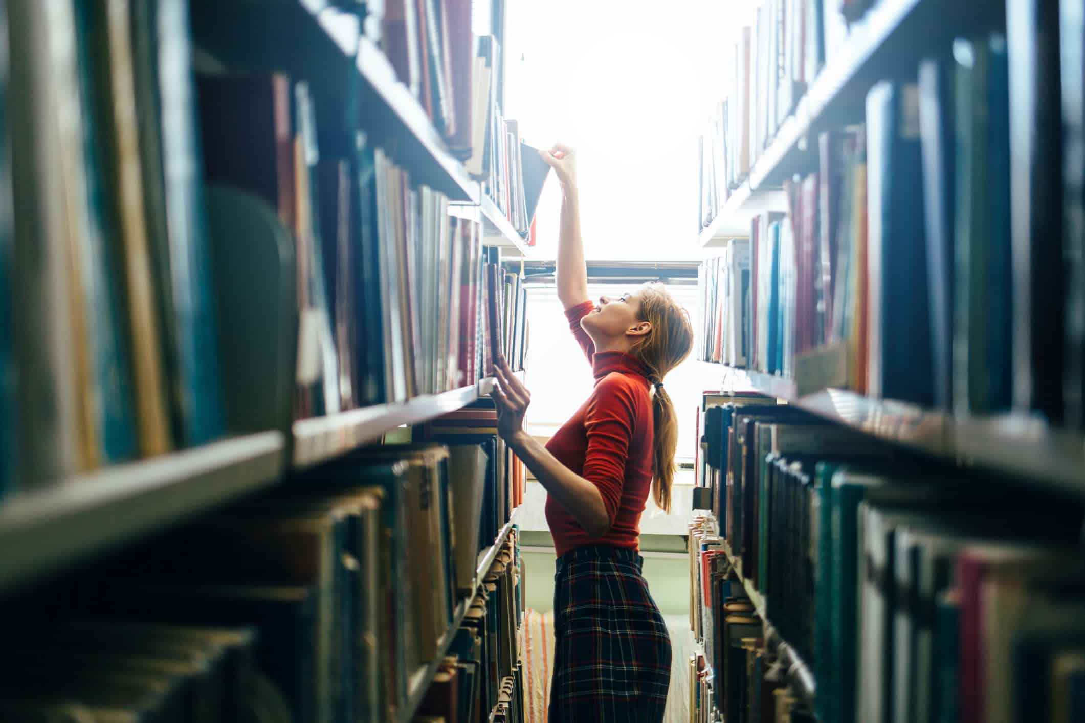 Young librarian searching books and picking one book from library bookshelf.