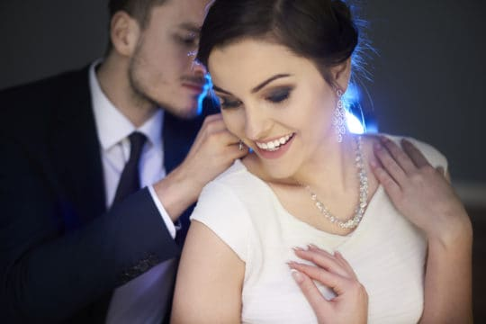 Loving man putting necklace. on girlfriend