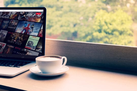 Netflix website showing on screen laptop with macbook pro at cafe.