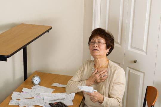 Senior woman feeling ill with her financial bills.