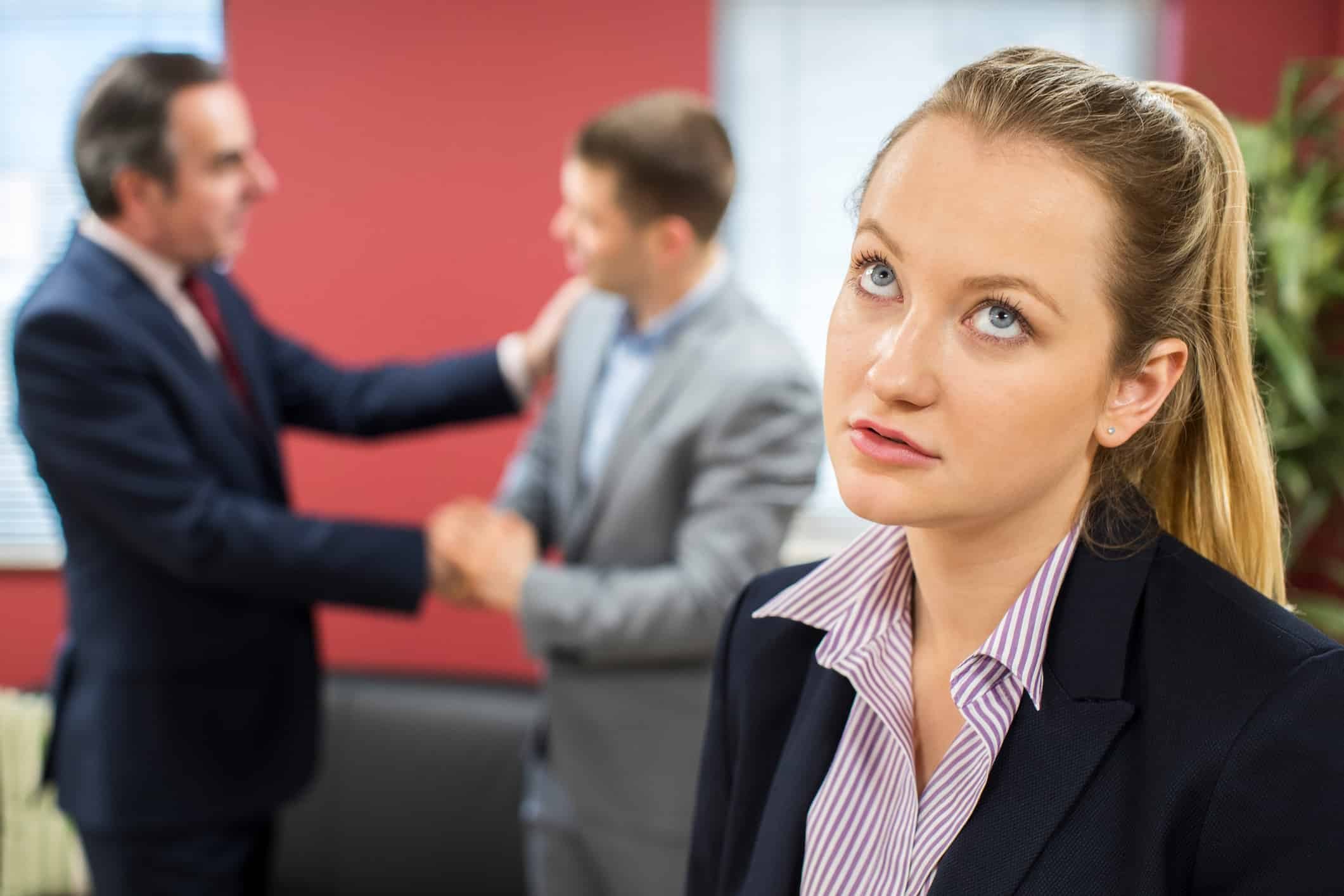 Unhappy businesswoman with male colleague being congratulated