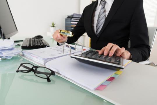 Businessman analyzing bills with magnifying glass