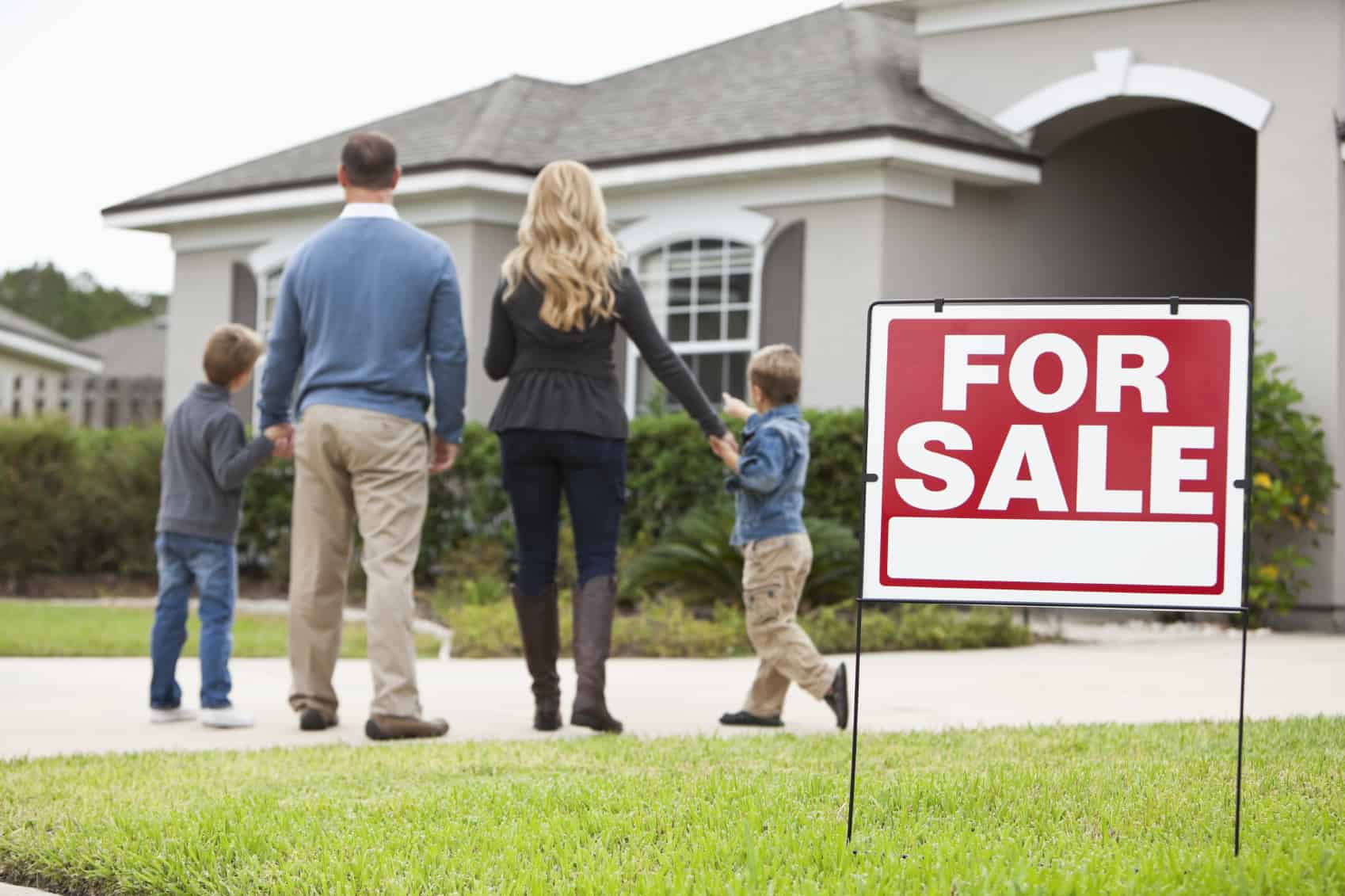 Family standing in front of house with FOR SALE sign in front yard.