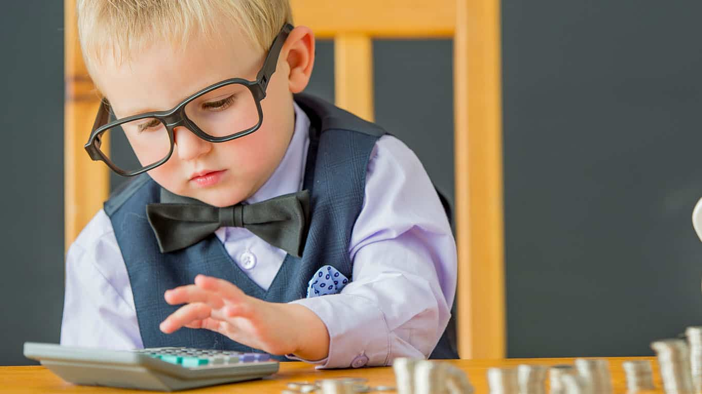 A child with glasses uses a calculator to count his coins