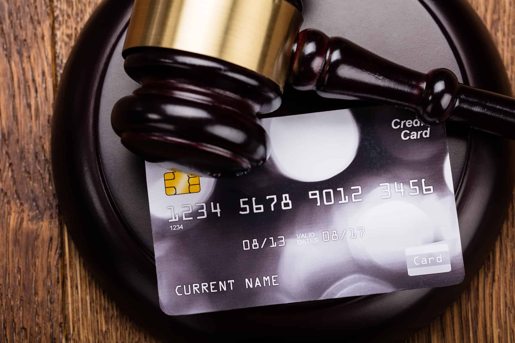 Credit card on wooden gavel at wooden desk in courtroom.