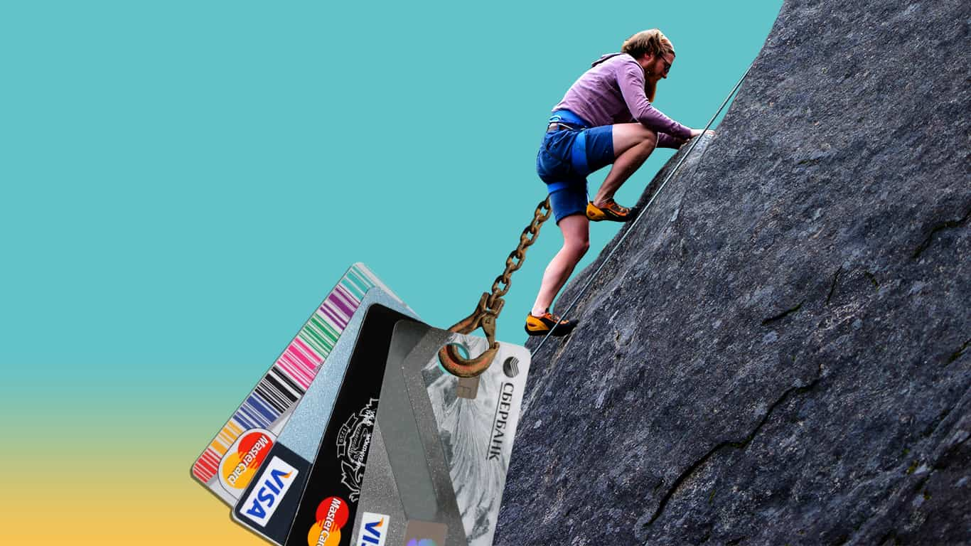 A man tries to scale a cliff chained to his credit card debt (illustrated)