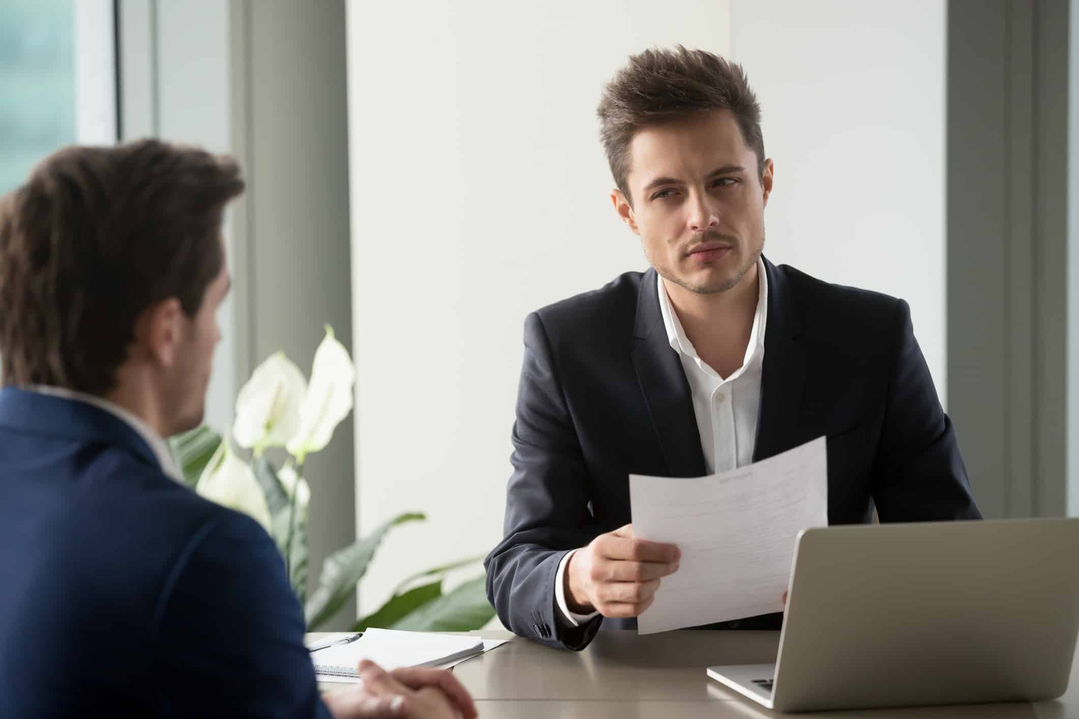 Distrustful hiring manager holding applicant's resume