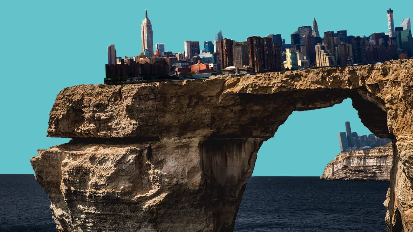 A city slides off a cliff toward the ocean (illustrated)