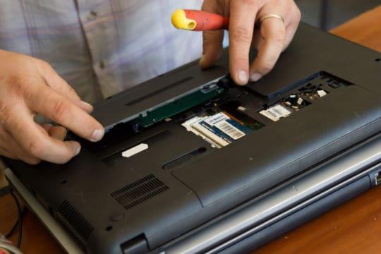 Technician repairing laptop computer