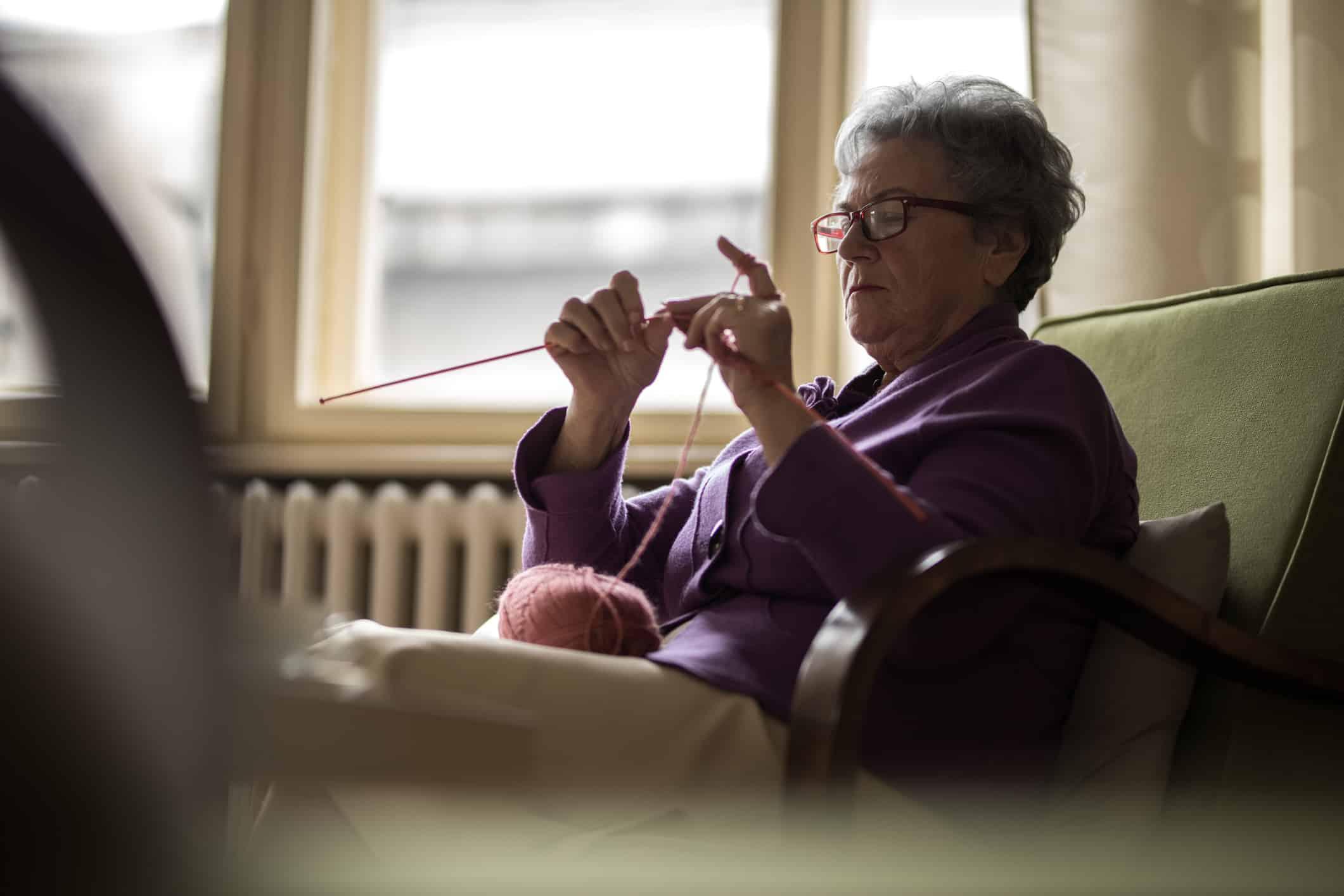 Senior women sitting at home and knitting near window.