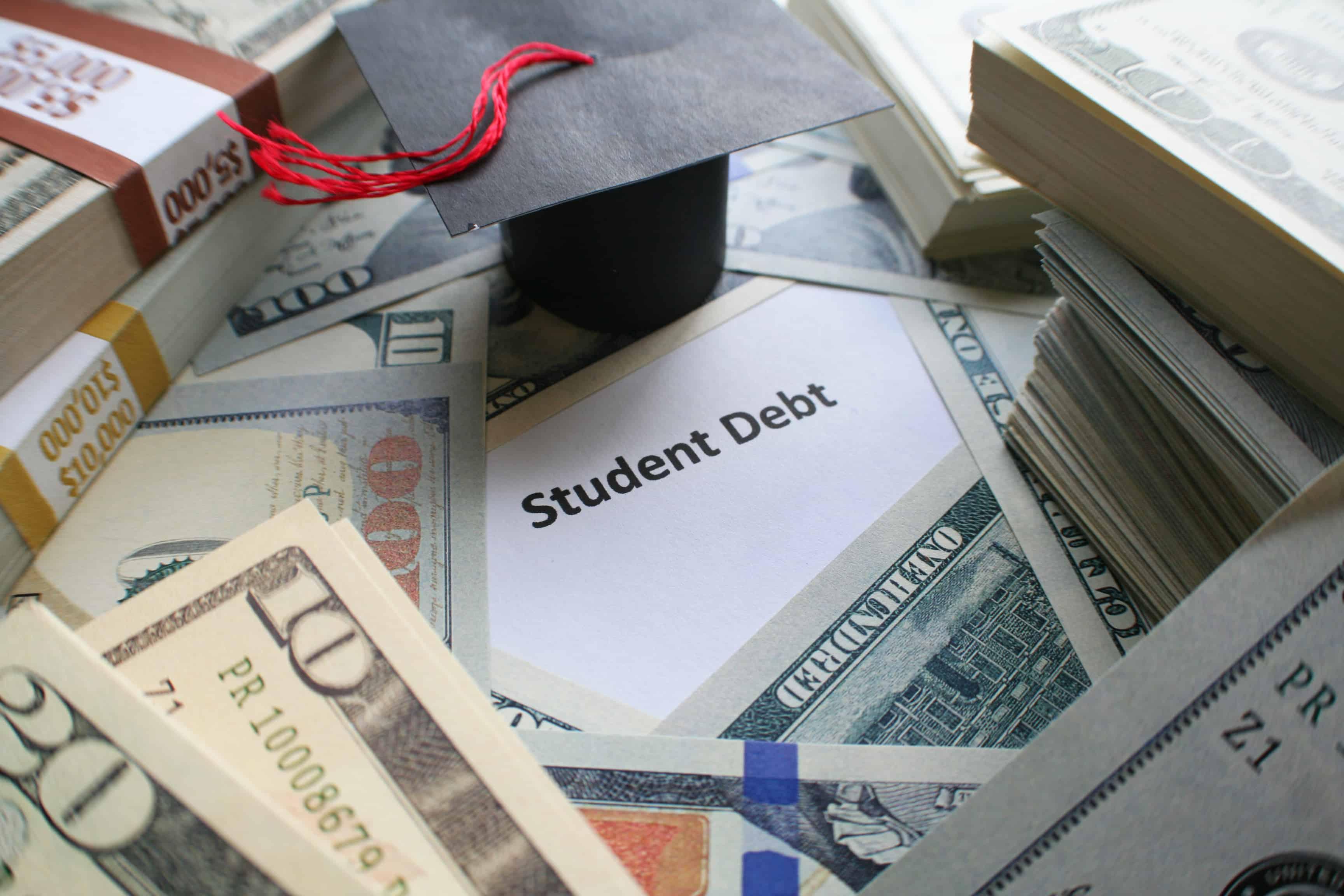 Graduation cap and cash sit on top paper reading