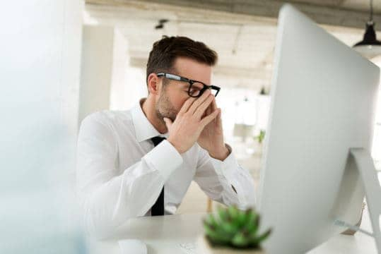 Worried businessman sitting at the desk in his office and using computer.
