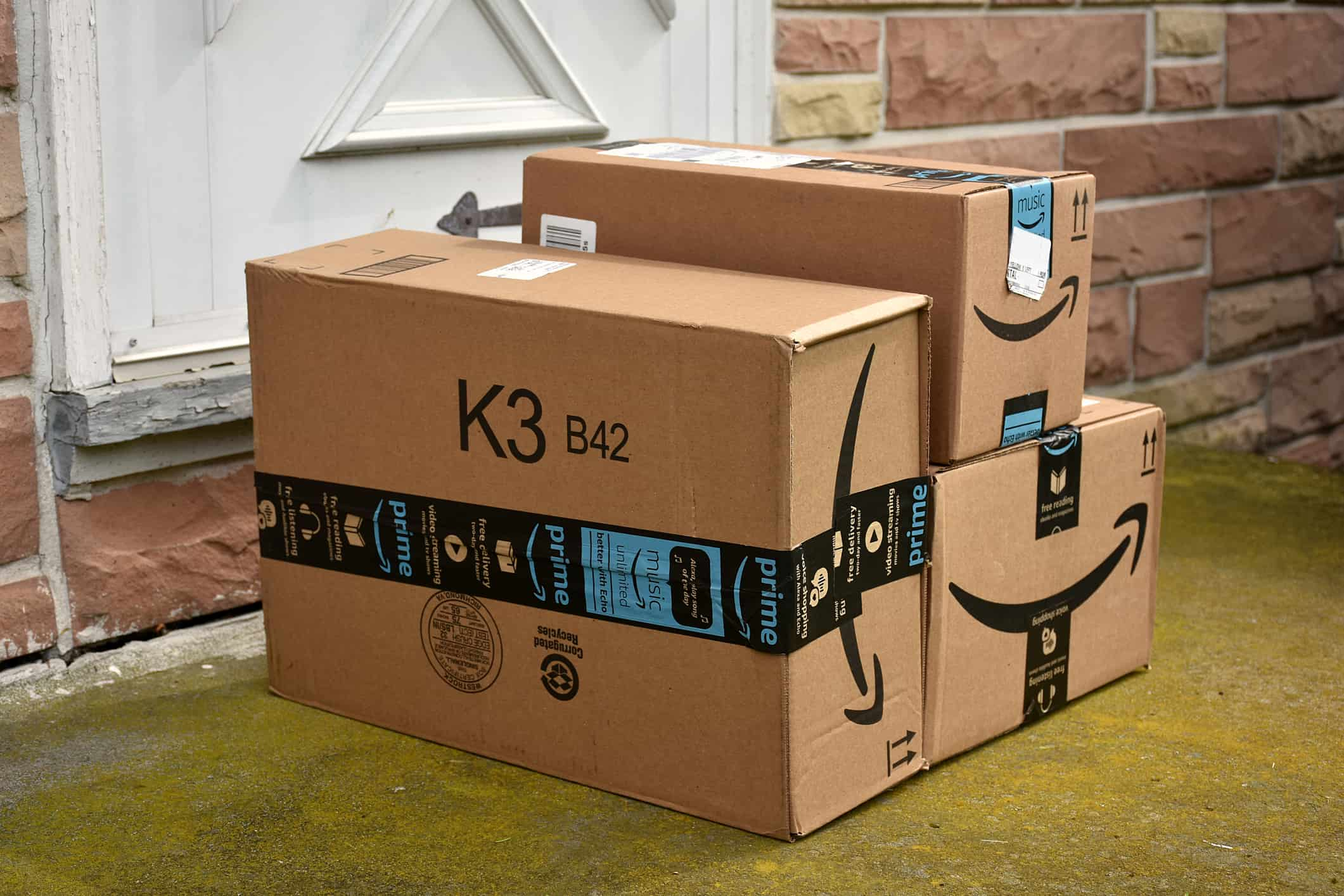 Amazon Prime boxes at front door of home.