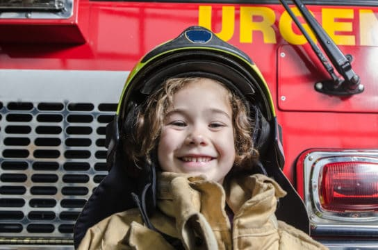 Young girl wearing fireman coat and helmet, smiling and standing in front of fire truck