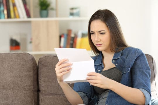 Worried woman reading a letter sitting on a couch in the living room at home.