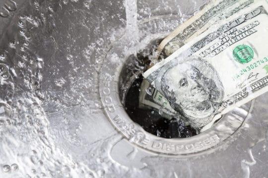 Money being washed down garbage disposal.