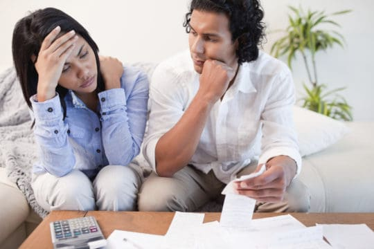 a couple appear to be upset and frustrated as they review their finances