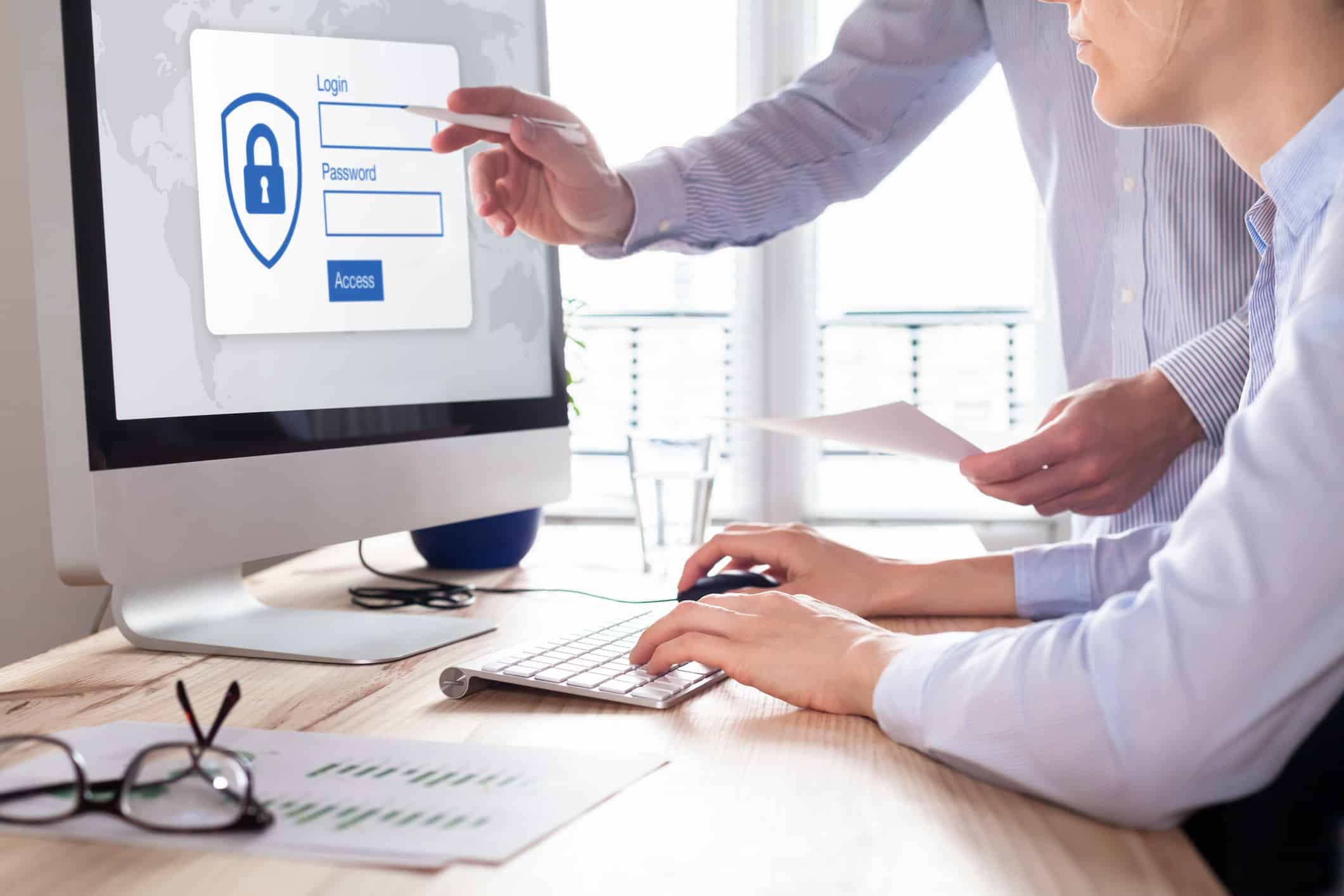 Manager providing authentication credentials (login, password) to business person to access confidential data on computer screen.