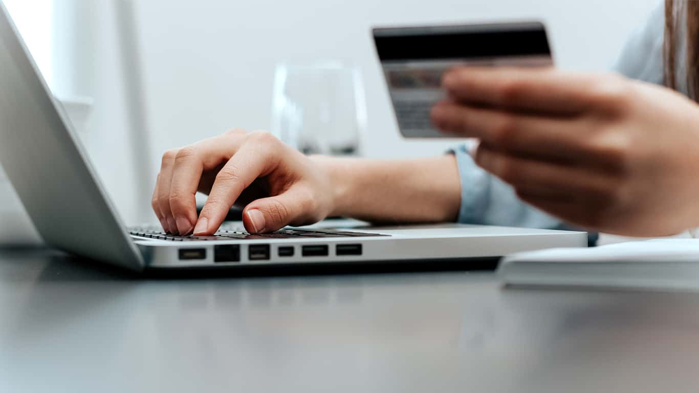 Woman's hands pay credit card bills on laptop