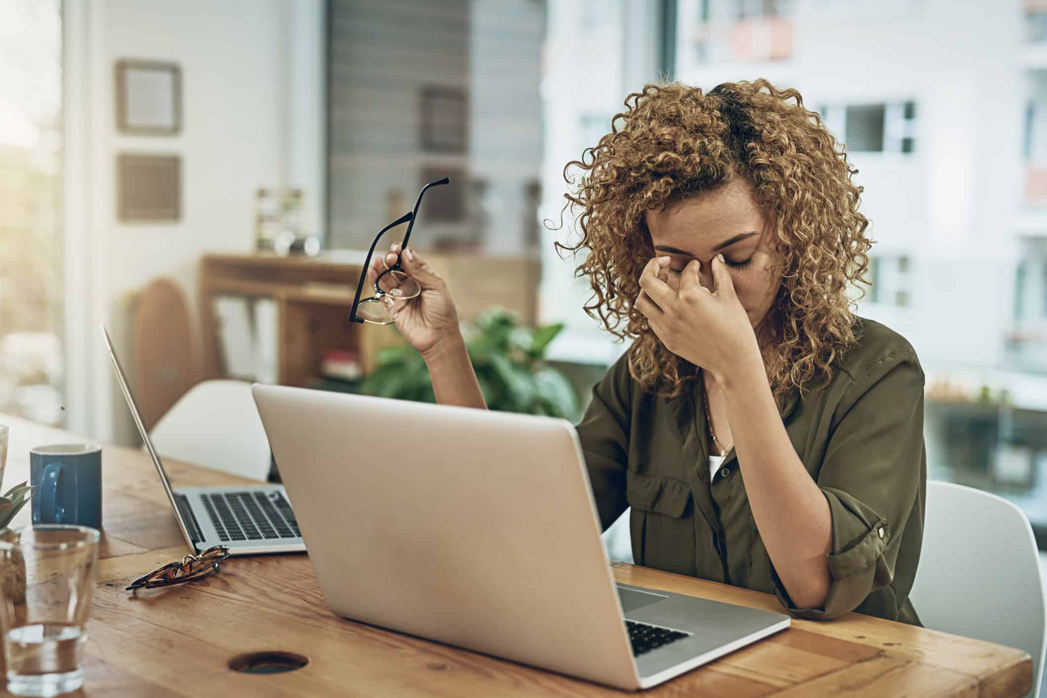 Shot of a young woman suffering from stress while using a computer at her work desk.