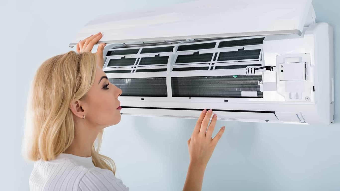 Young Woman Checking Air Conditioner Mounted On Wall At Home