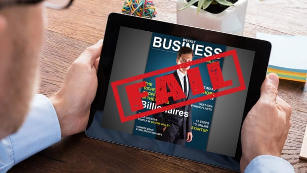 Man looking at ipad with business magazine on cover with FAIL over it