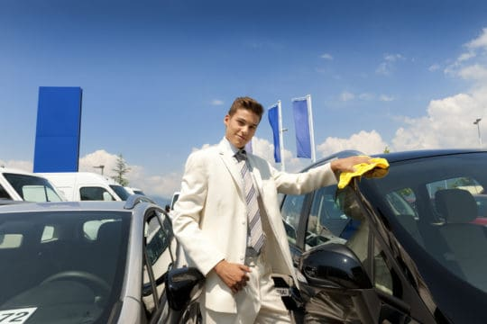 Car salesman shining a new car with yellow cloth, dressed in a white suit.