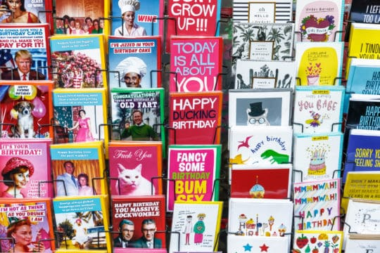 Quirky birthday cards on display at grocery store.