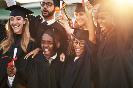 Shot of a group of cheerful university students on graduation day unaware of looming student debt