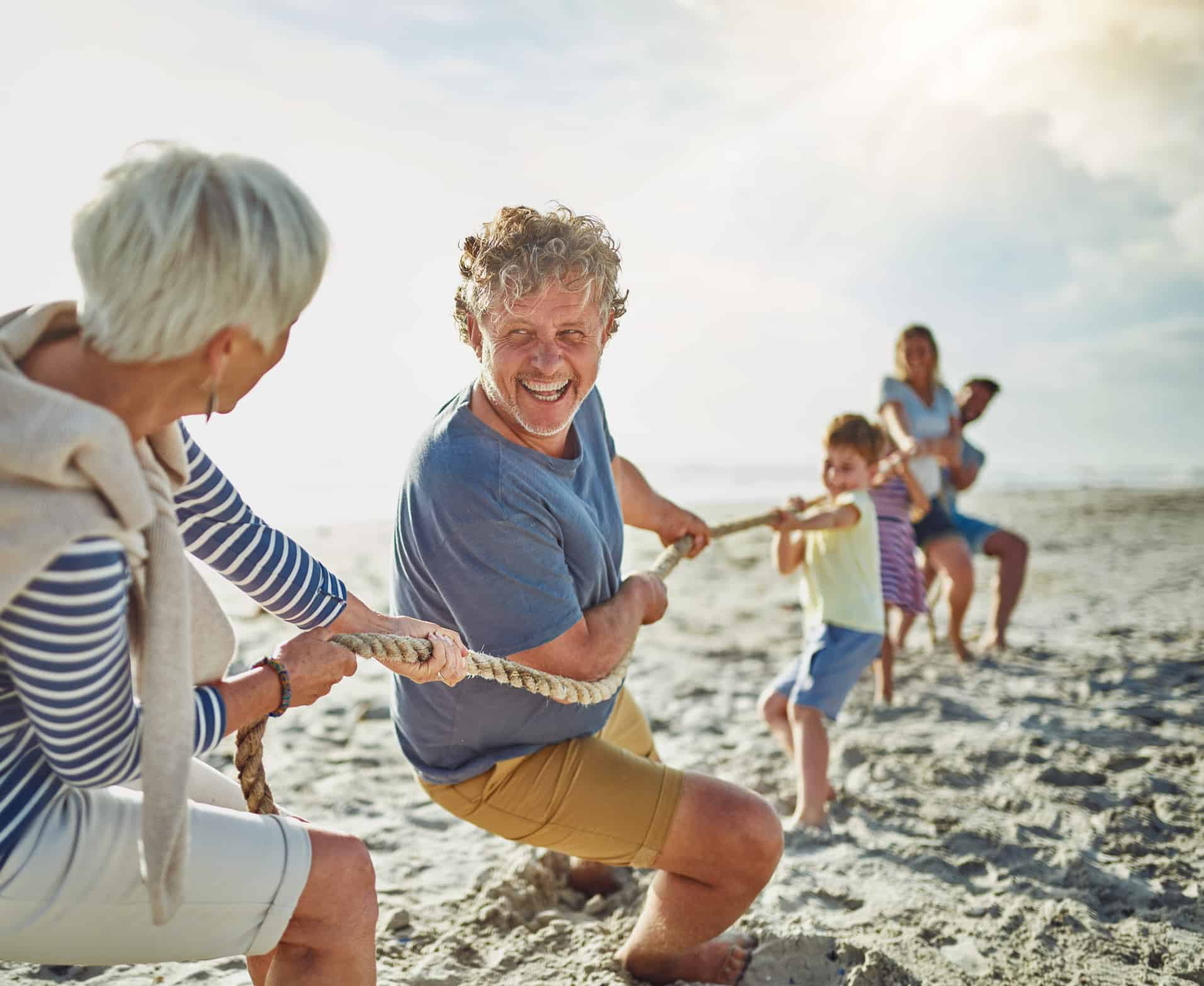 Shot of a happy multi-generational family with money having a tug of war on the beach
