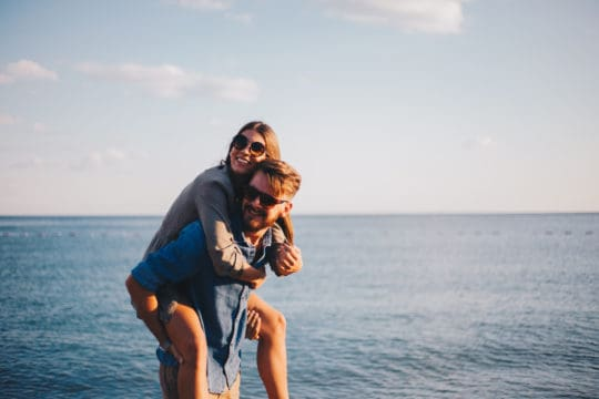 Modern couple on the beach hugging and loving each other
