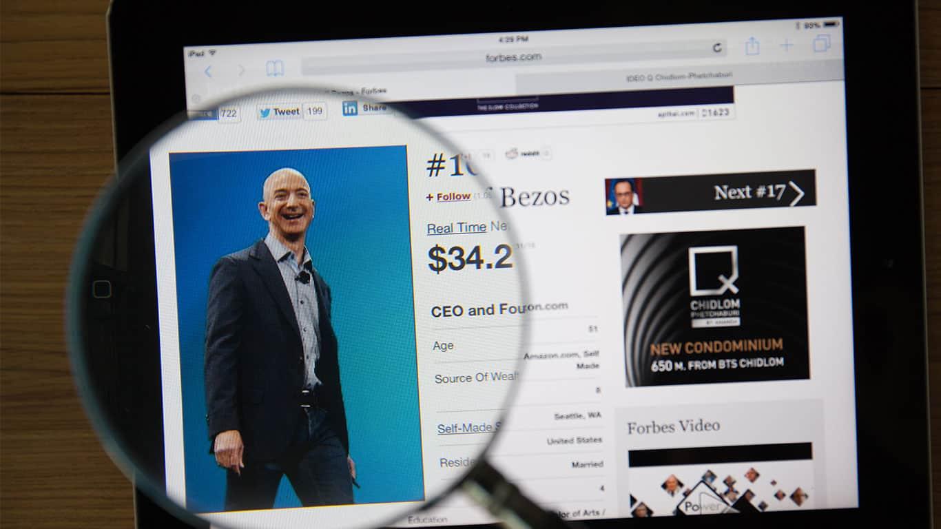 Jeff Bezos on a ipad monitor screen through a magnifying glass