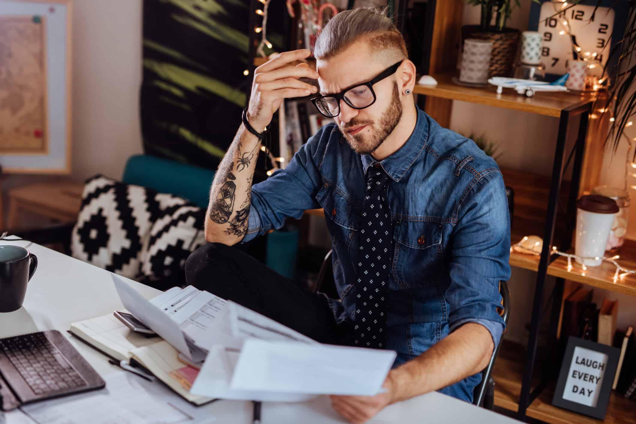 Millennial entrepreneur reviews paperwork.