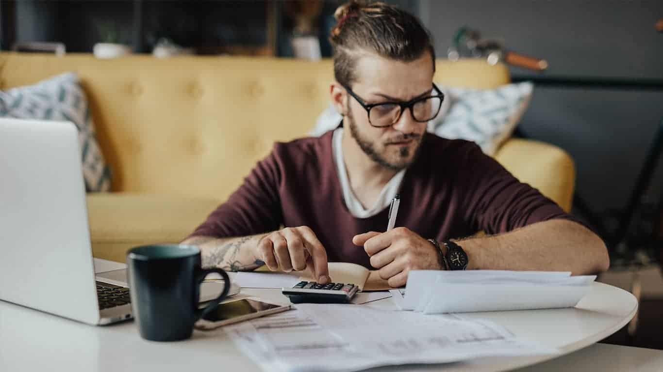 Concentrated young student using online banking to pay the bills