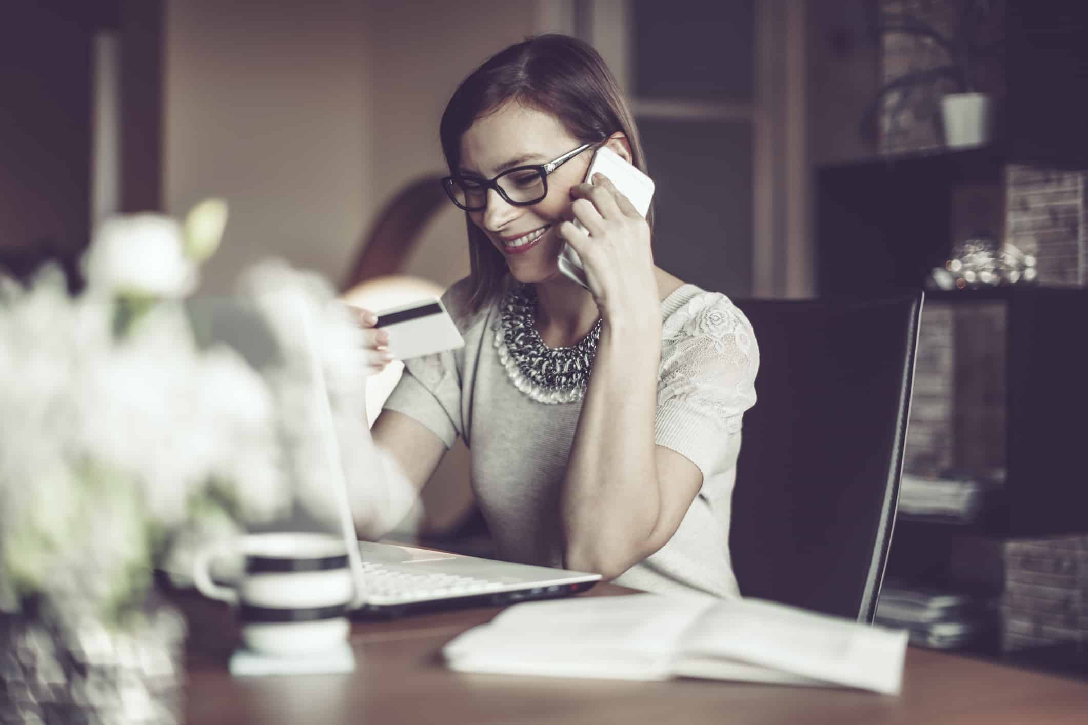 Young woman on phone with credit card company; how often is your credit score updated