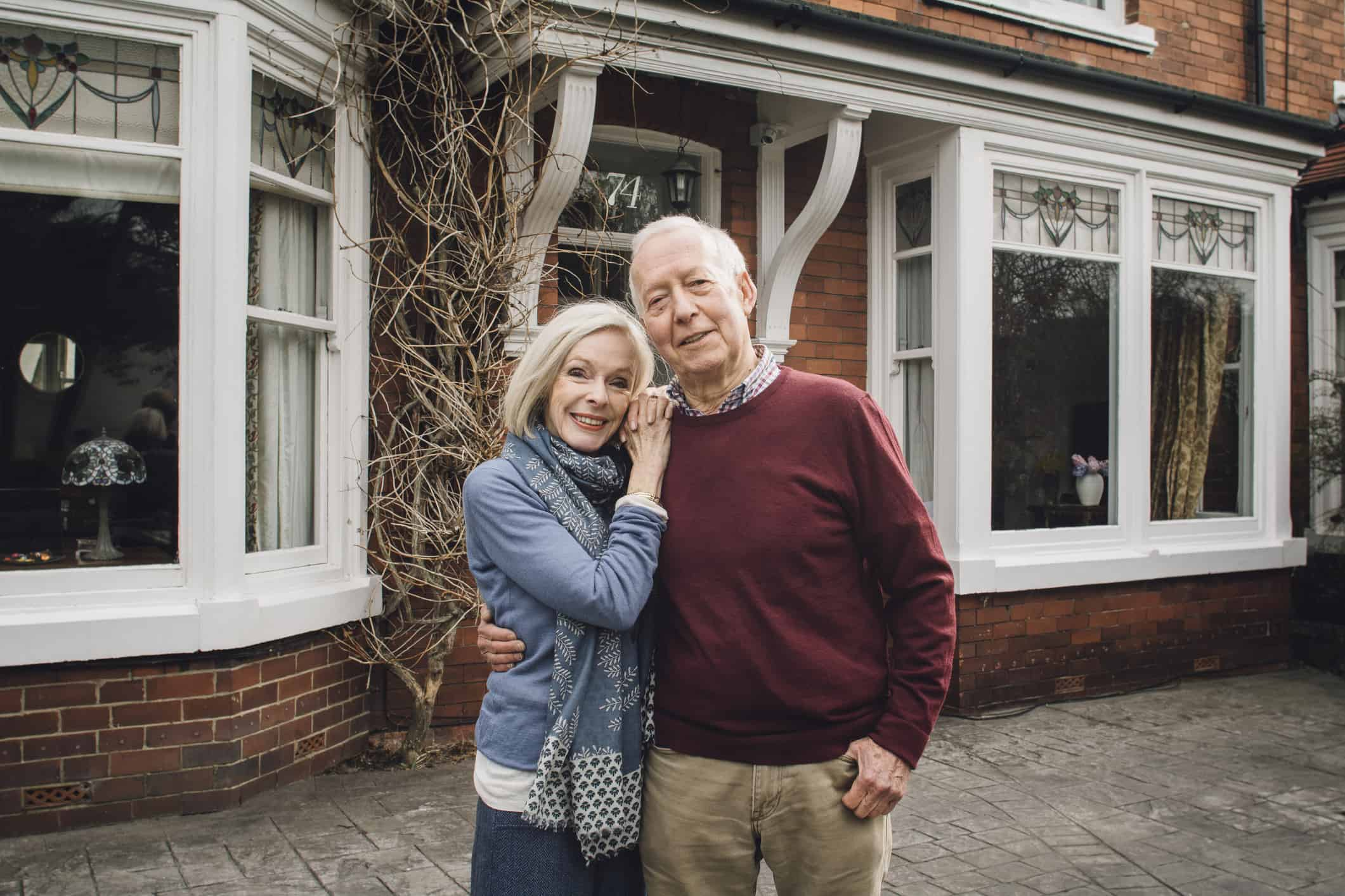 Senior couple are smiling for the camera while standing in front of their newly bought home.