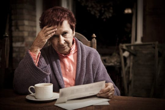 Senior woman seated at the table with a cup of coffee distressed over the costs of her bills.
