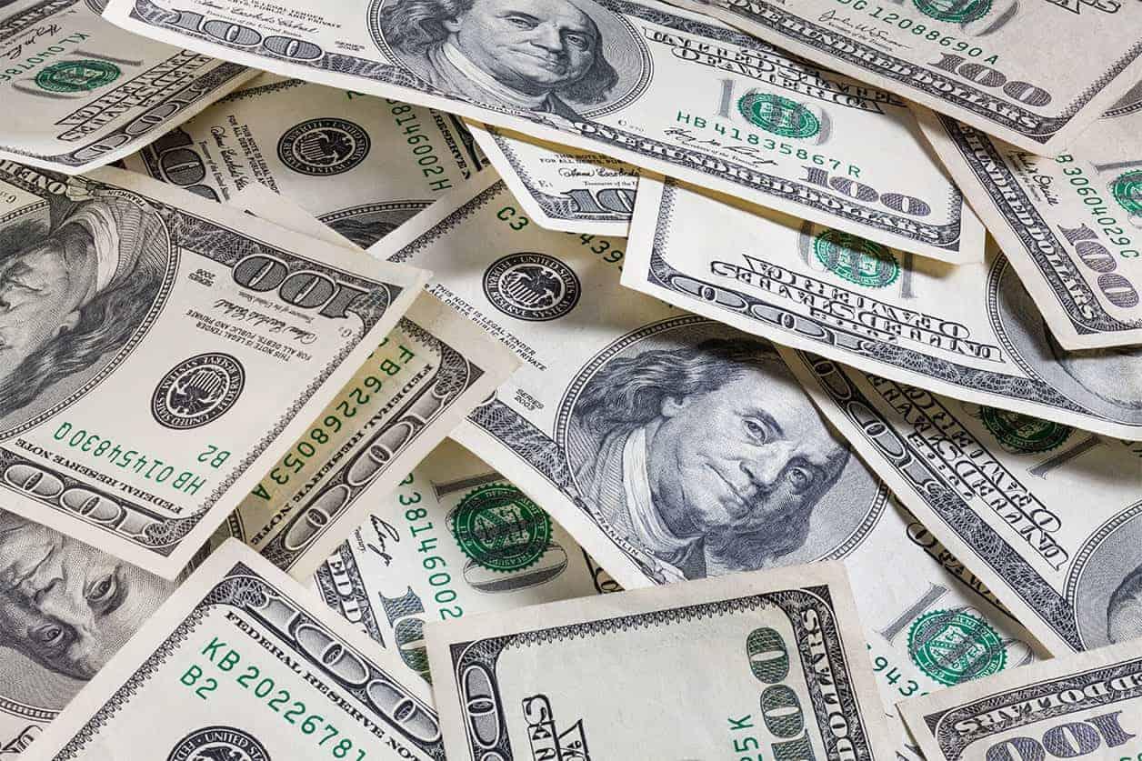 debt settlement vs. debt management. Set of 100 dollar bills as background for money theme.