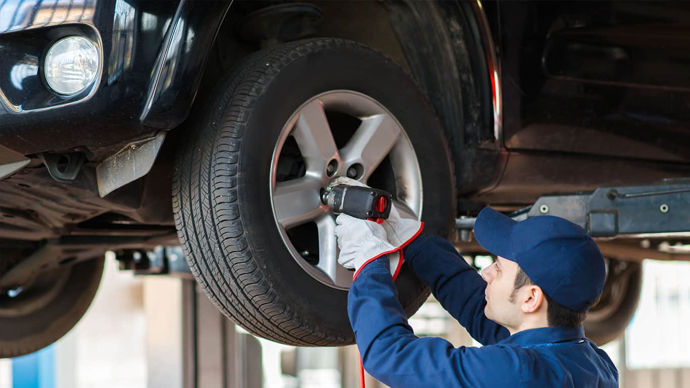 Mechanic screwing on a costly tire at tire shop