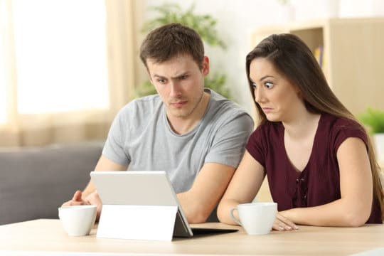 Confused couple receiving on line news sitting in a desk at home