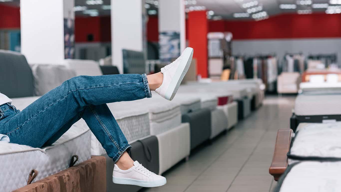 Woman sitting on mattresses kicking her legs
