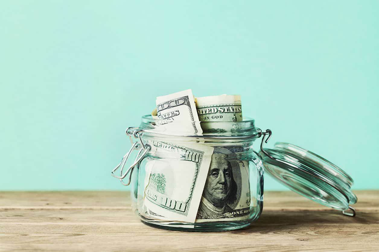 Dollar bills in glass jar. Saving money, economy, finance concept