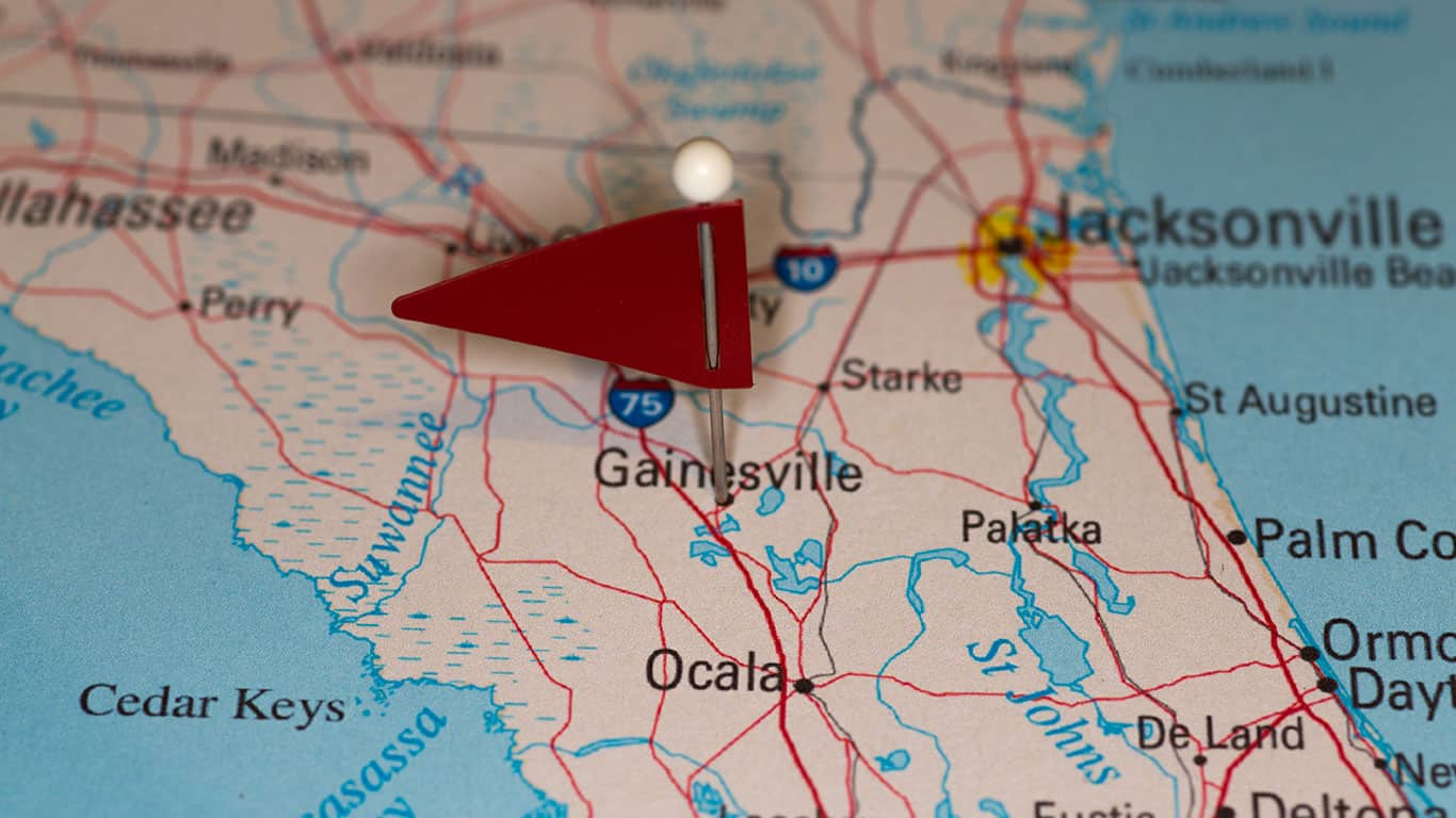 A map pin with a red flag pinpoints the city on a select area from a high quality map.